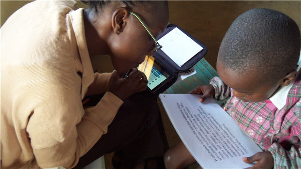 Photo showing a teacher using Tangerine to record student reading test results in Kenya.