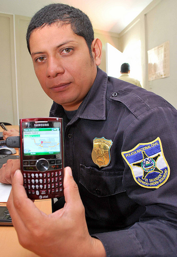 A PNC police officer demonstrating the Ushahidi smart phone client.